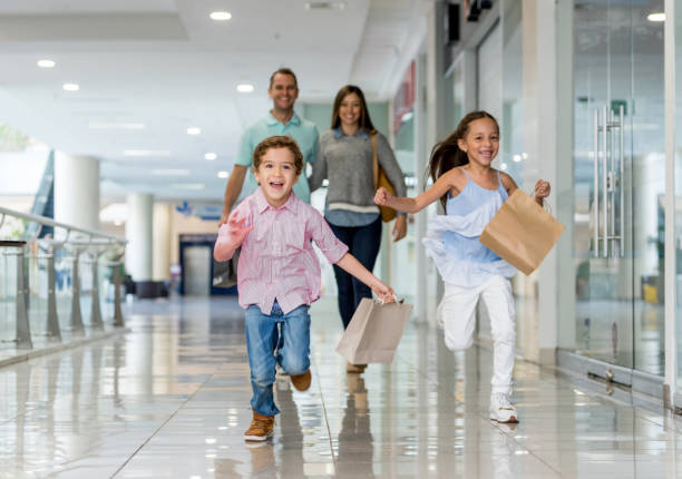Family shopping and running towards the camera at the mall stock photo