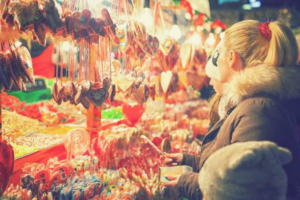 familie shopping am weihnachtsmarkt - lutscher cookies stock-fotos und bilder