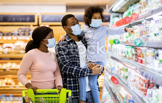 Family shopping during coronavirus pandemic. African American family with child wearing face masks, purchasing food at supermarket, panorama. Black parents with their kid buying products at mall