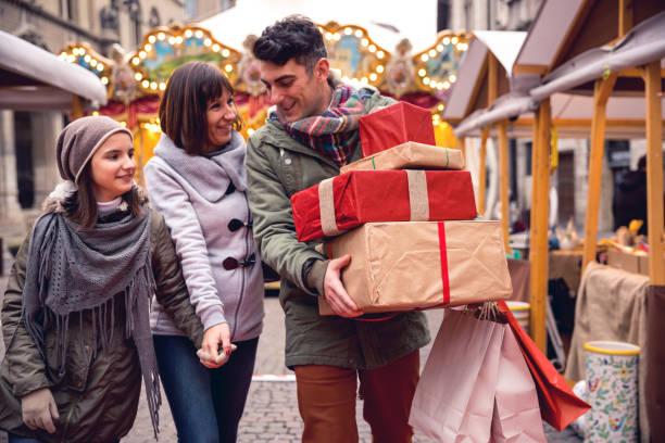 familie, einkaufen in beschäftigt und dekorierten stadtstraße in weihnachten - kinder verpackung stock-fotos und bilder