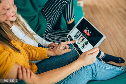 Young woman sitting on the sofa with her family and shopping online with digital tablet.