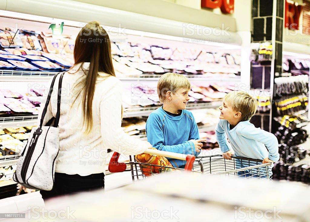 Family shopping trip; playful children and mother in supermarket royalty-free stock photo
