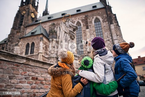 Mother with three kids sightseeing city of Brno. Family is photographing the Cathedral of St. Peter and Paul in the old town of Brno. Nikon D850
