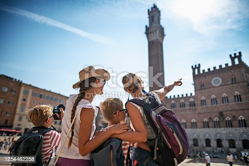 Mother and three little tourists sightseeing Siena. The kids are standing in Piazza del Campo. Little boys is taking photos of Torre del Mangia and Palazzo Pubblico visible in the background. Sunny Summer day. Nikon D850