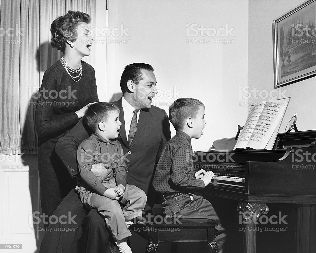 Family singing around piano royalty free stockfoto