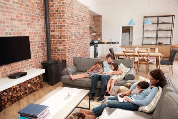family sit on sofa in open plan lounge mit technologie - kinderküche zubehör stock-fotos und bilder