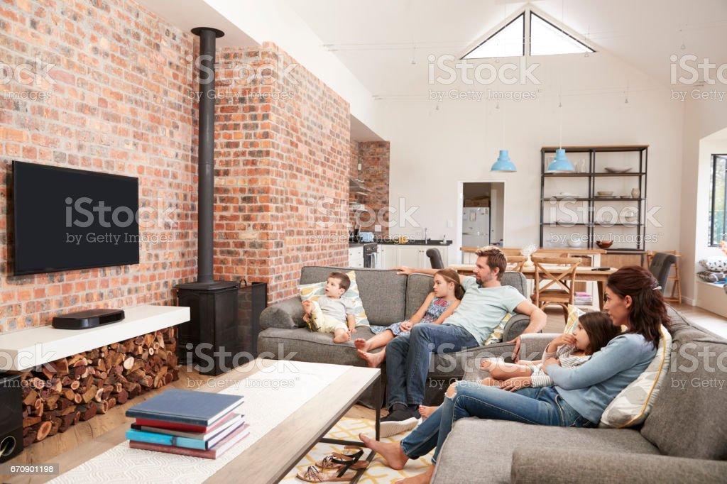 Familie Sitzen Auf Sofa In Offenes Wohnzimmer Vor Dem Fernseher Stockfoto  und mehr Bilder von 9-9 Monate