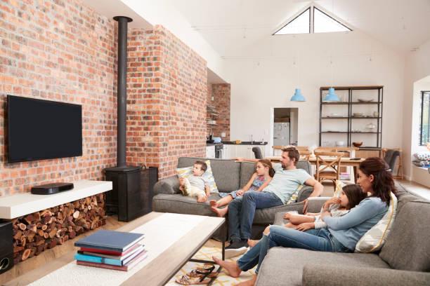 familie sitzen auf sofa in offenes wohnzimmer vor dem fernseher - kids tv zimmer stock-fotos und bilder