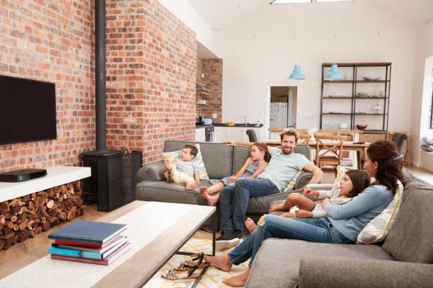 family sit on sofa in open plan lounge watching television - zimmer bildschirm stock-fotos und bilder