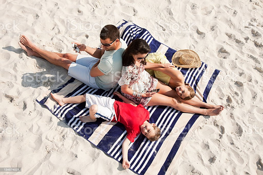 Family sitting and lying together on a rug on a beach stock photo