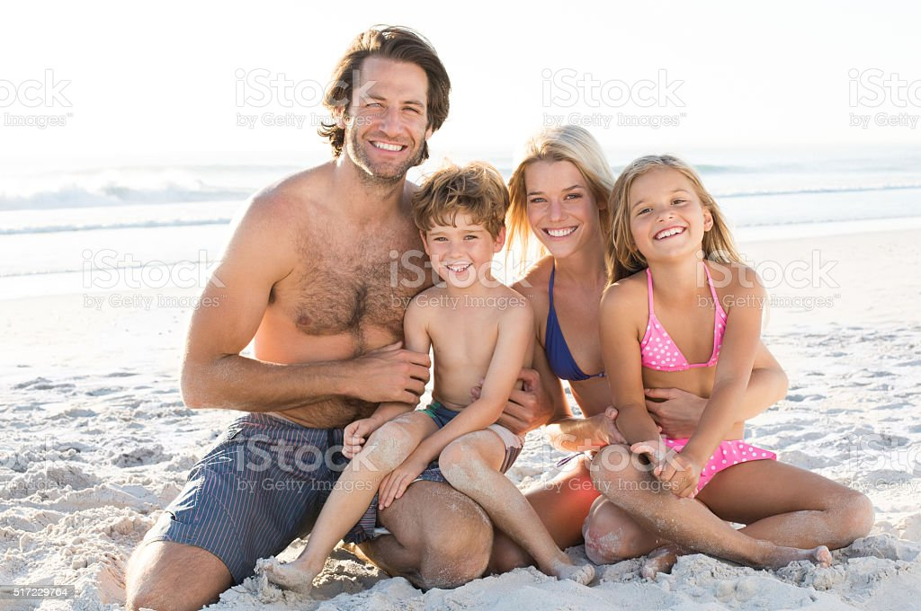 Family sitting at beach stock photo