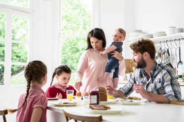 family sitting at breakfast table, mother holding baby boy, father and girls eating food - busy stock photos and pictures