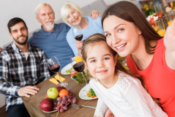 Family sitting at home, making selfie together and smiling wide stock photo