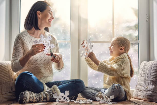 family sitting by the window - winter stock pictures, royalty-free photos & images