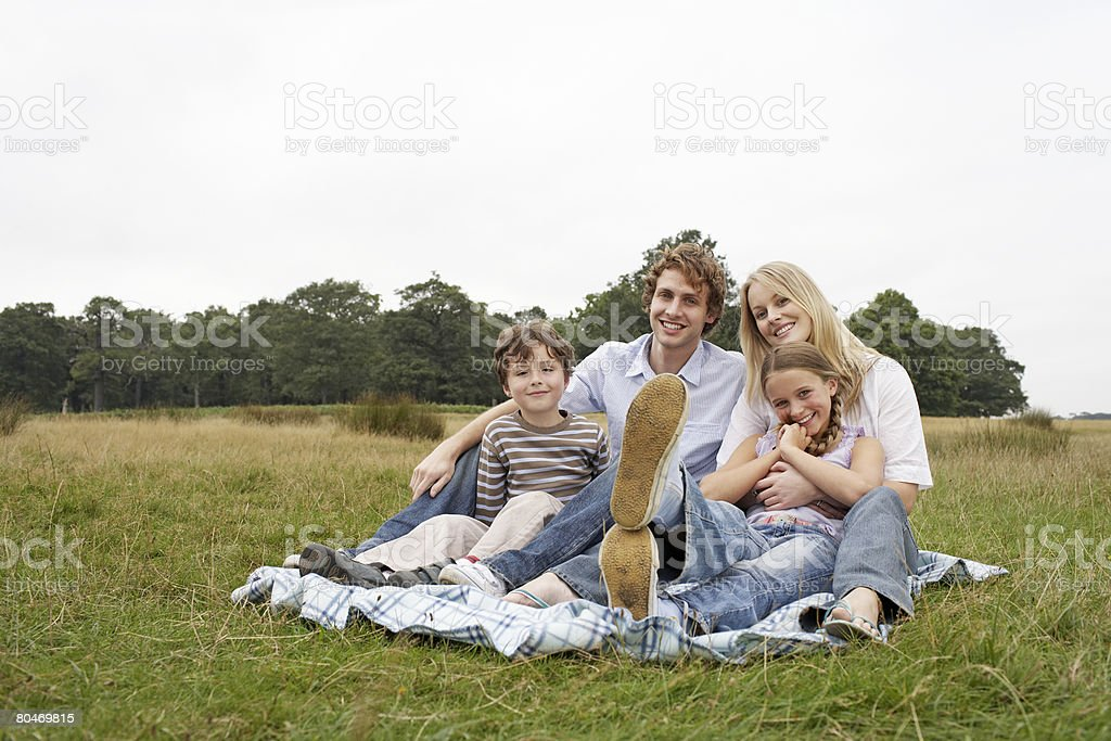 Family sitting in a field Lizenzfreies stock-foto