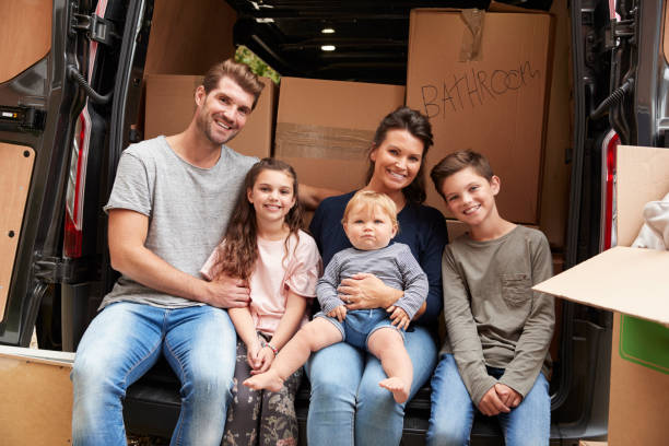 Family Sitting In Back Of Removal Truck On Moving Day stock photo