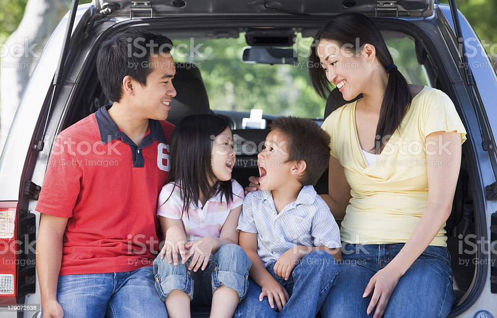 Family sitting in back of van smiling stock photo