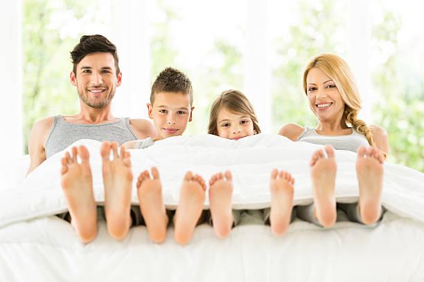 Familia sentada en la cama juntos - foto de stock