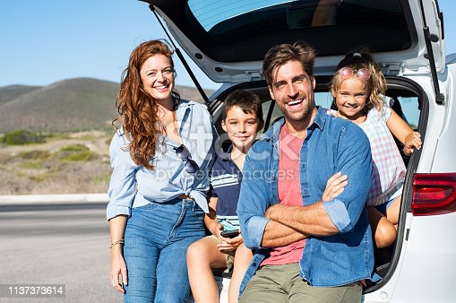 972962180 istock photo Family sitting in car trunk 1137373614
