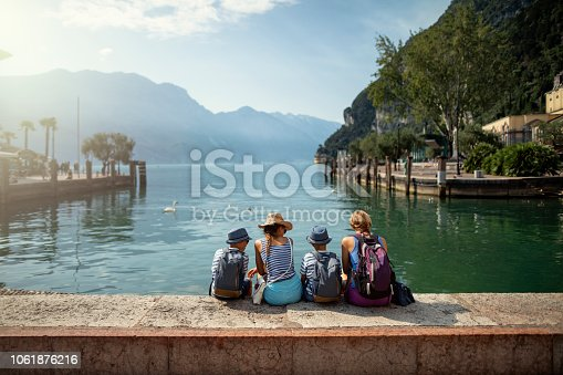 Family enjoying Garda Lake vacations. They are sitting in harbor of Riva del Garda and enjoying view of Lake Garda. Nikon D850