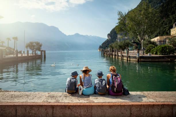 Familie sitzen im Hafen von Riva del Garda und genießen die Aussicht auf den Gardasee – Foto