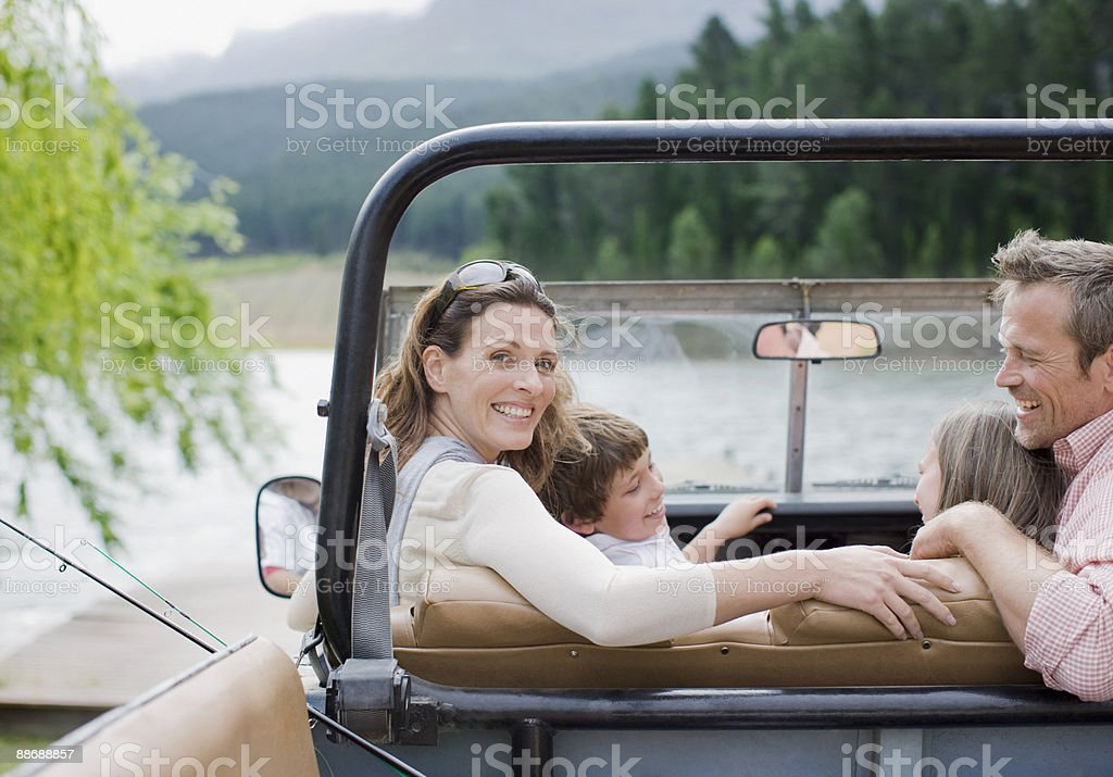 Family sitting in jeep near lake royalty-free stock photo
