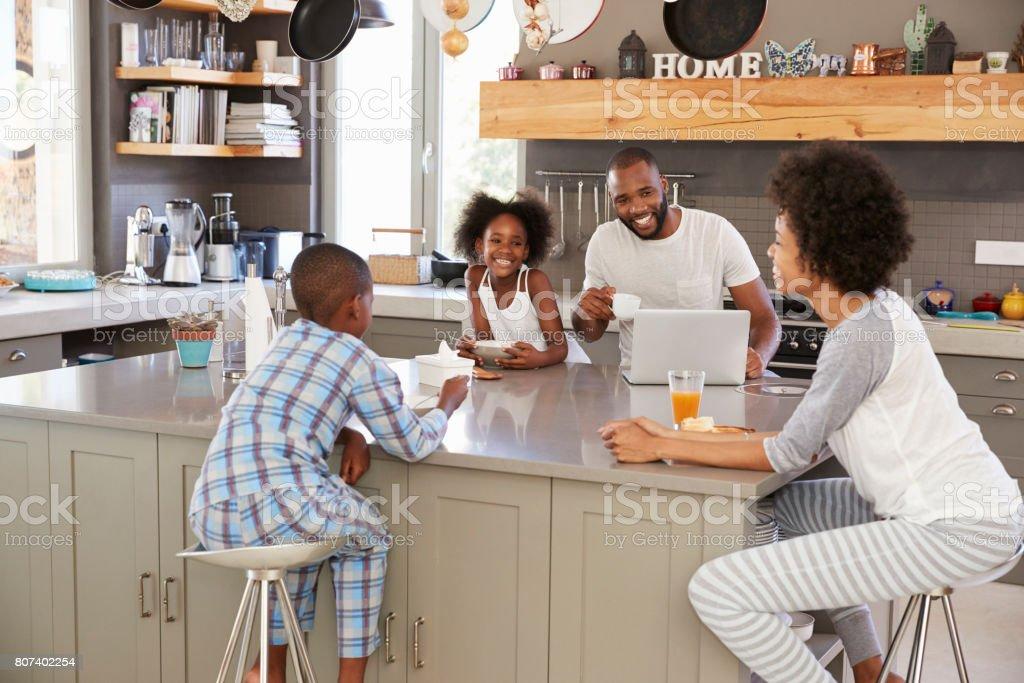Family Sitting In Kitchen Enjoying Morning Breakfast Together stock photo