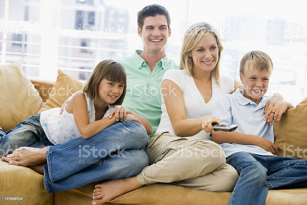 Family sitting in living room with remote control royalty-free stock photo
