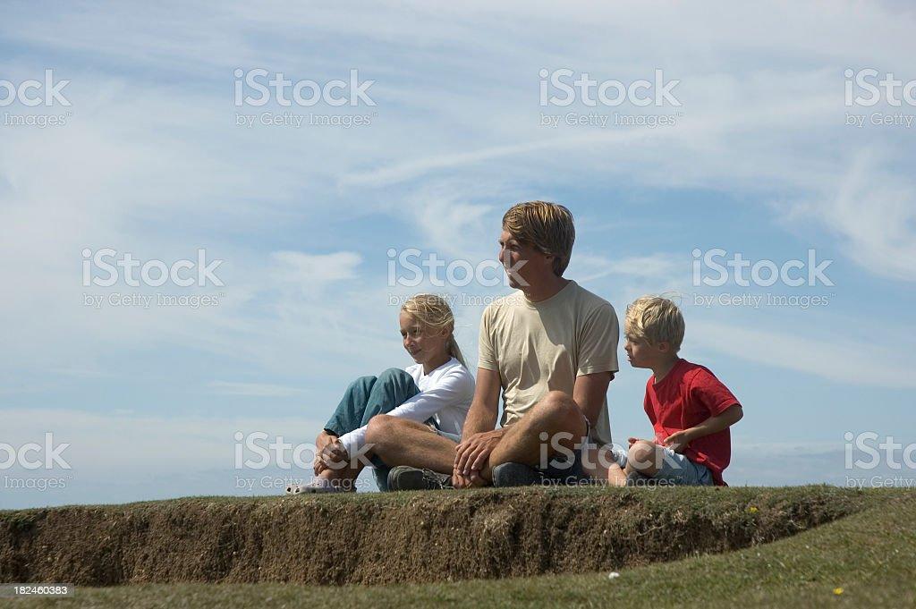 Familia sentada en el césped foto de stock libre de derechos