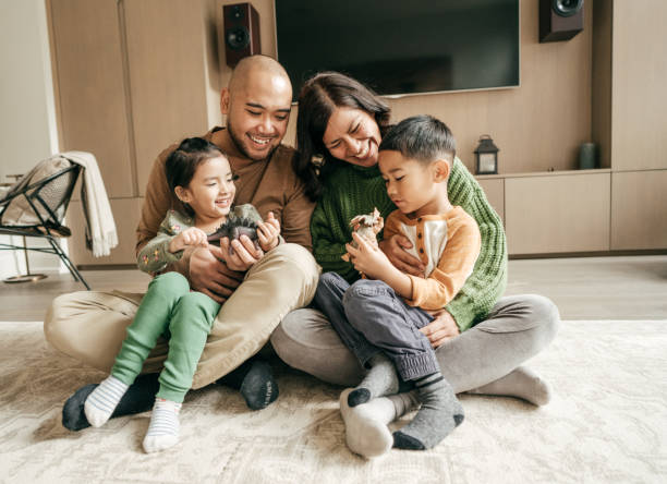 Family sitting in the living on the floor Hispanic Family together southeast asian ethnicity stock pictures, royalty-free photos & images