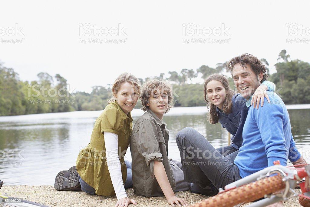 Family sitting near lake royalty-free stock photo