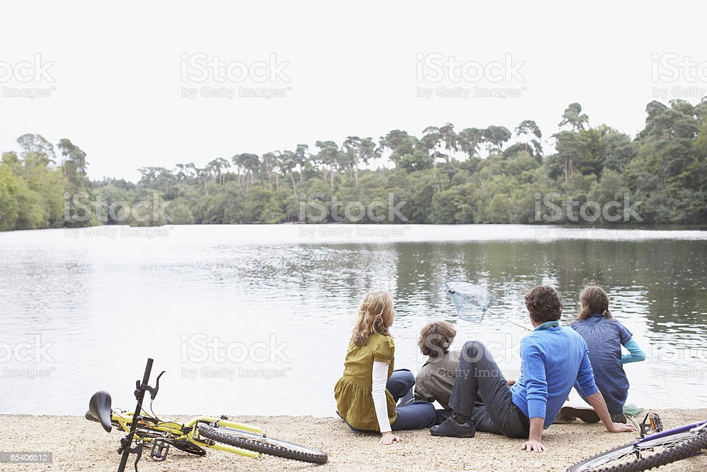 Family sitting near lake royalty-free stock photo