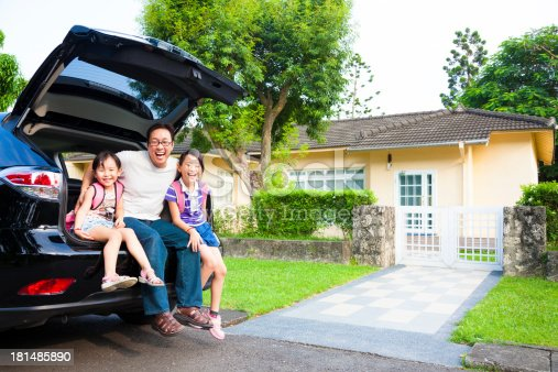istock Family sitting on back of car in front of house 181485890