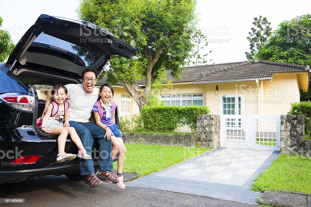 Family sitting on back of car in front of house stock photo