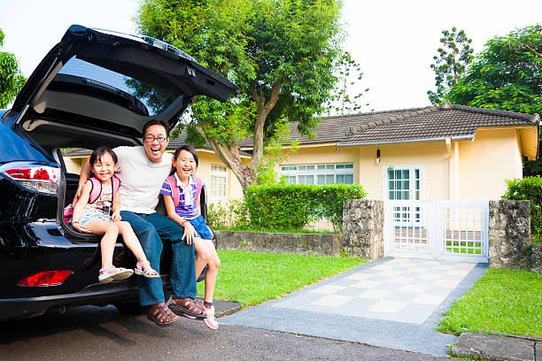família sentada em volta de automóvel em frente de casa - nova casa - fotografias e filmes do acervo