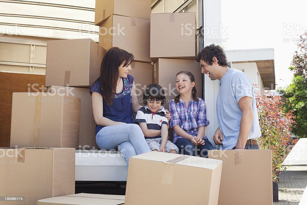Family sitting on back of moving van stock photo
