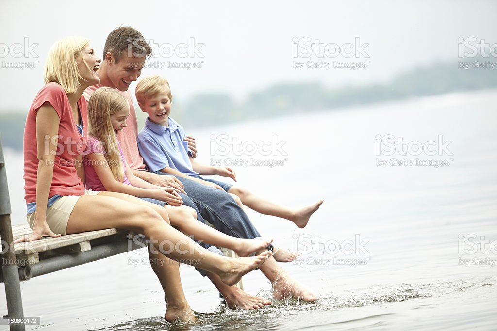 Family sitting on boardwalk at lakeside stock photo