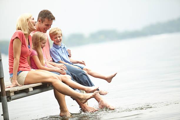 family sitting on boardwalk at lakeside - flod vatten brygga bildbanksfoton och bilder