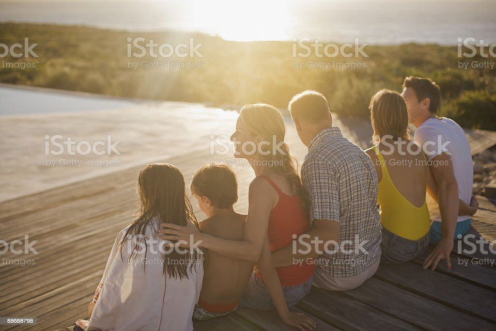 Family sitting on deck by swimming pool stock photo