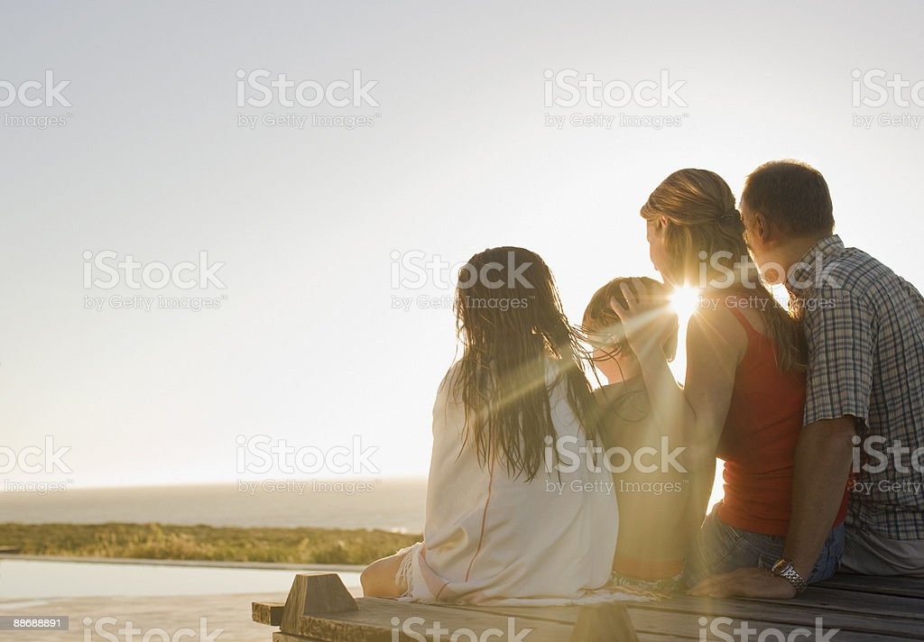 Family sitting on deck in afternoon sun royalty-free stock photo