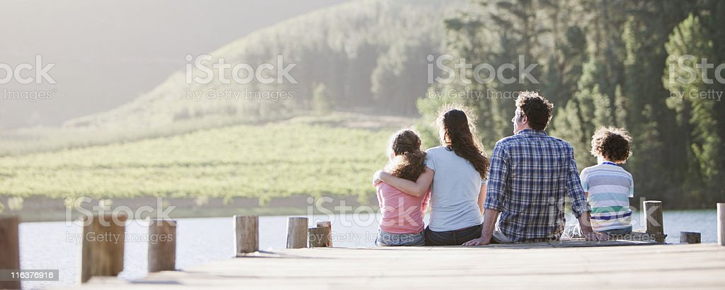 Family sitting on dock by lake stock photo
