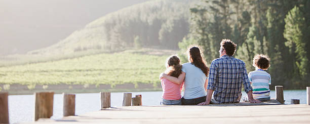 family sitting on dock by lake - pier stock photos and pictures