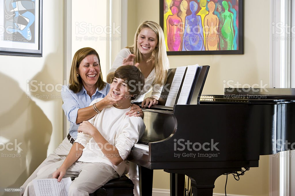 Family sitting on piano bench, mother teasing son royalty-free stock photo