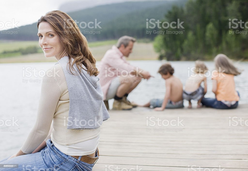 Famille assis sur le quai près du lac photo libre de droits