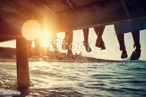 Five people having fun sitting on pier. Feet shot from below the pier. Sunny summer day evening. Nikon D850