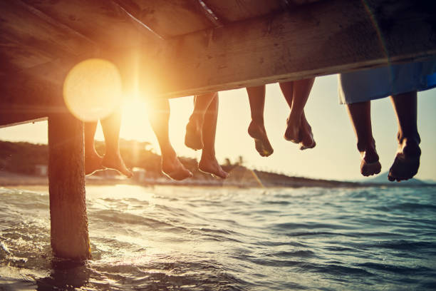 Family sitting on pier by the sea Five people having fun sitting on pier. Feet shot from below the pier. Sunny summer day evening. Nikon D850 dusk stock pictures, royalty-free photos & images