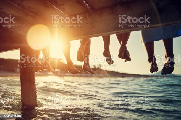 Photo of Family sitting on pier by the sea
