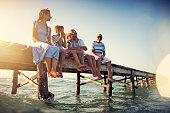 Grandparents and grandchildren having fun sitting on pier. Sunny summer day evening.\nNikon D850