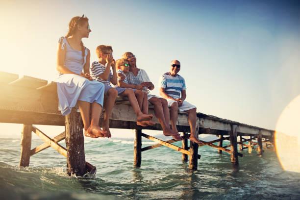 familjen sitter på piren vid havet - spain solar bildbanksfoton och bilder