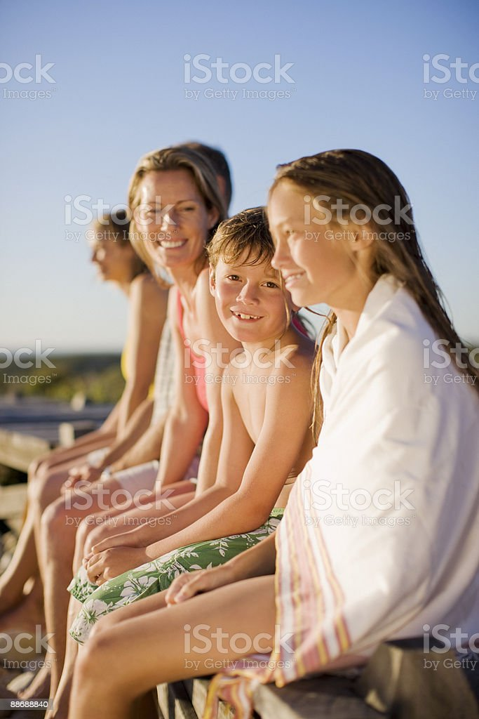 Family sitting on pier near beach royalty-free stock photo
